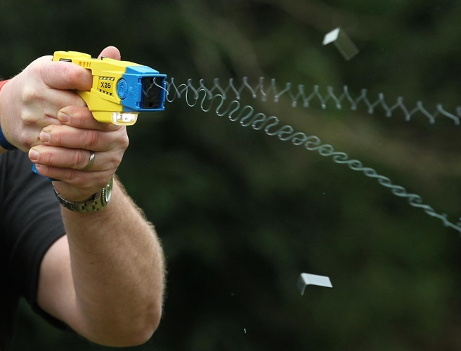 File photo dated 26/02/13 of a police officer using a Taser, as police chiefs called for an independent review into the safety of Tasers after an inquest found that the use of a 50,000-volt stun gun contributed to the death of a young man.